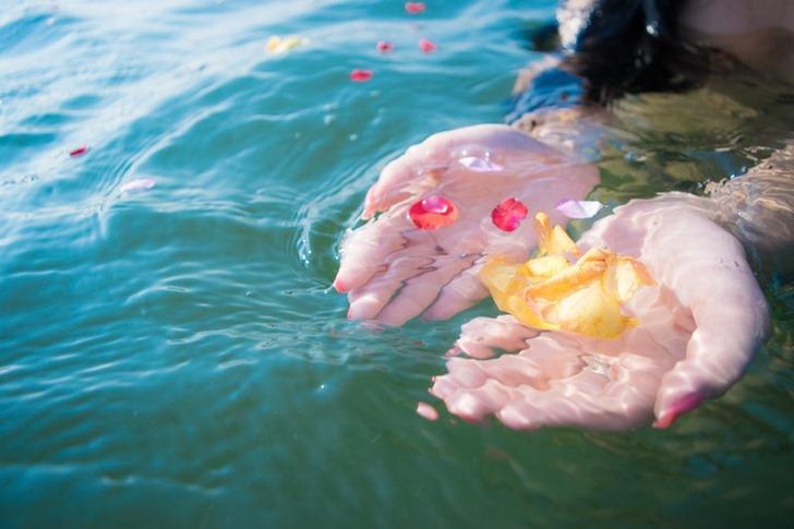 水中の花びらをすくう女性